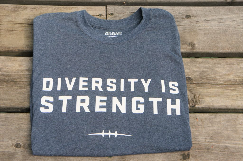 grey shirt with diversity is strength written on the front